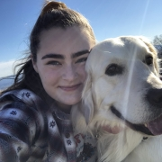 Girl hugging white golden retriever outside