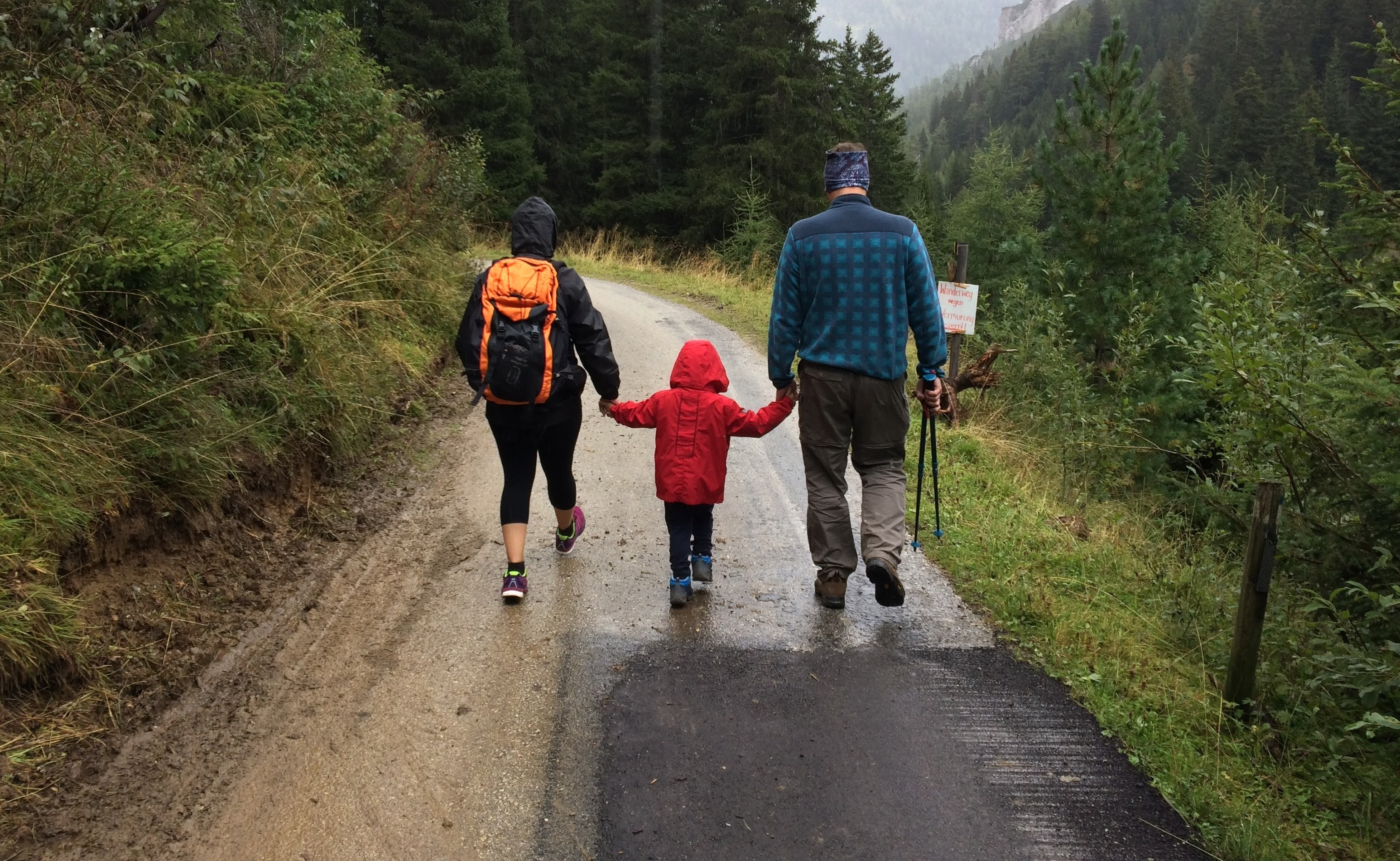 A mother and father walking down a trail outside with their child