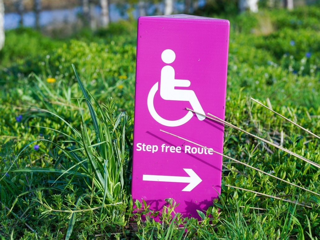"Pink handicap sign that reads ""step free route"" sitting in the grass"